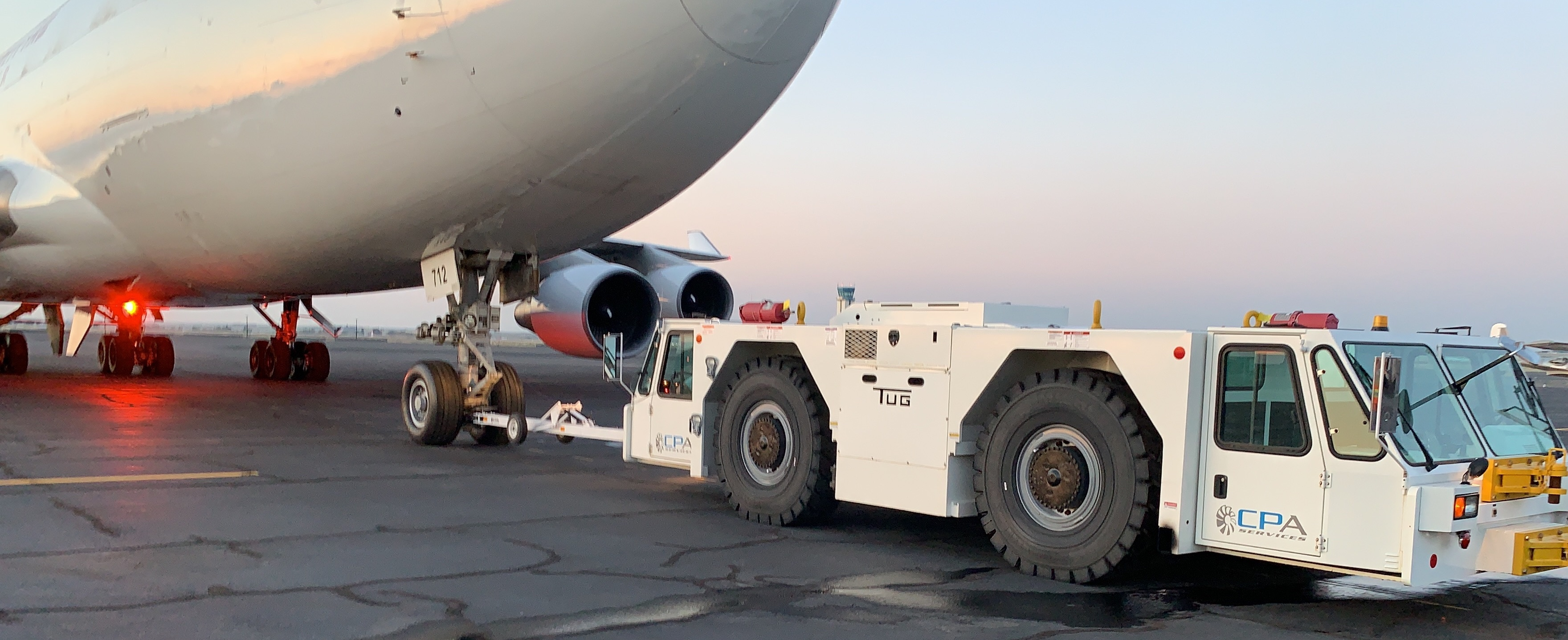 TUG/Textron GT110 pushback tug pushing back a loaded B747.